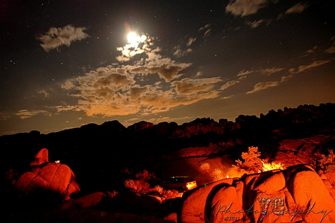A starry night as the campfire shines on the large boulders encompassing the campsites at Joshua Tree National Park, in Joshua Tree, Calif., on September 3, 2011. (Photography by Vicente Guerrero)