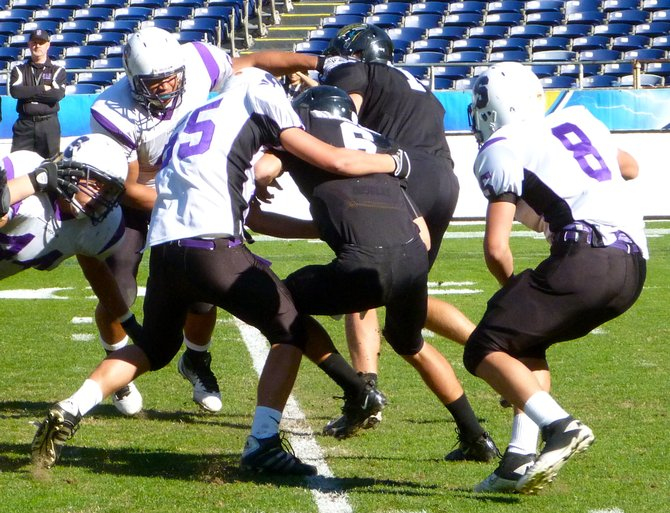A trio of Santana defenders wrap up Valley Center quarterback Ryan Kleiman