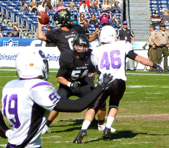 Valley Center quarterback Ryan Kleiman fires a pass with Jaguars lineman Torrey Denver keeping a Santana defender out