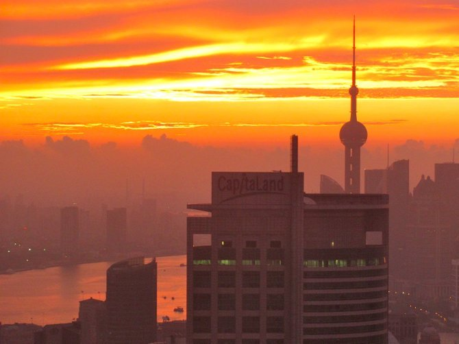 Sunrise over Shanghai. Last August I went to Shanghai for the first time. Because I hadn't adjusted to the time zone change, I worked through the night. I just happened to look up from my computer at the right time and saw  this magnificent view. I grabbed my camera quick!