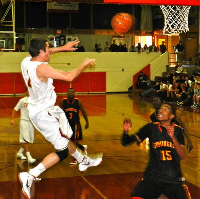 Torrey Pines guard Joe Rahon fires a pass across the lane over the head of Dominguez guard T.J. Traylor