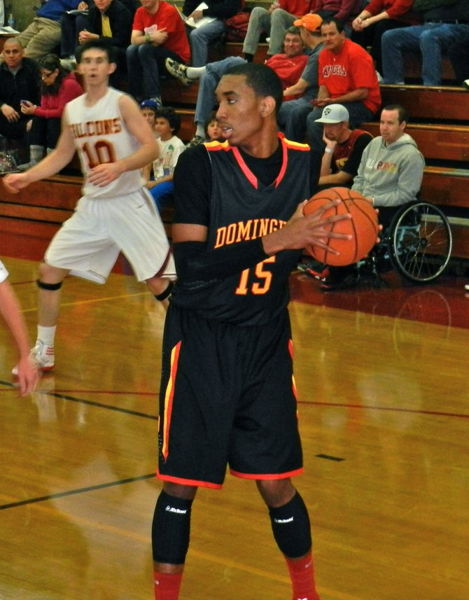 Dominguez guard T.J. Traylor shields the ball from Torrey Pines defenders in the backcourt