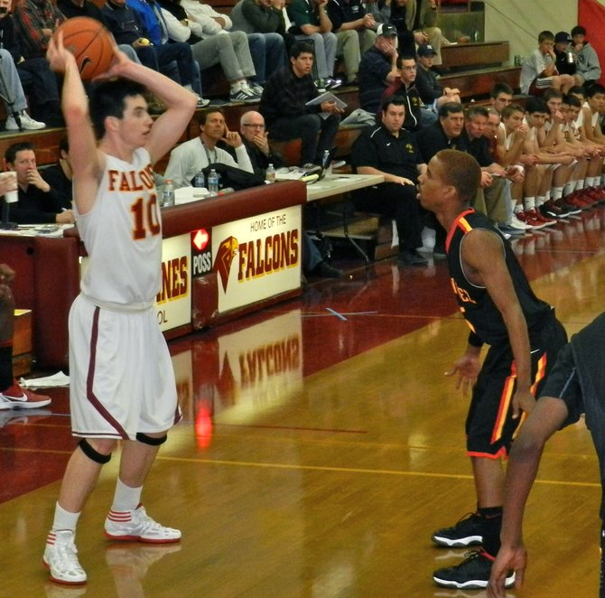Torrey Pines guard Garrett Galvin looks for a teammate with Dominguez guard E.J. Johnson defending