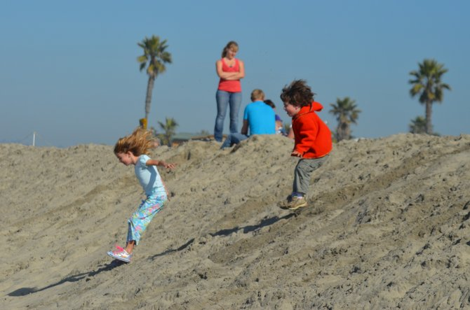 My kids leaping in tandem from a sand dune at Ocean Beach