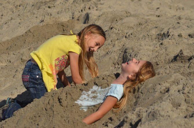 My daughter being buried in sand by her cousin, on Ocean Beach