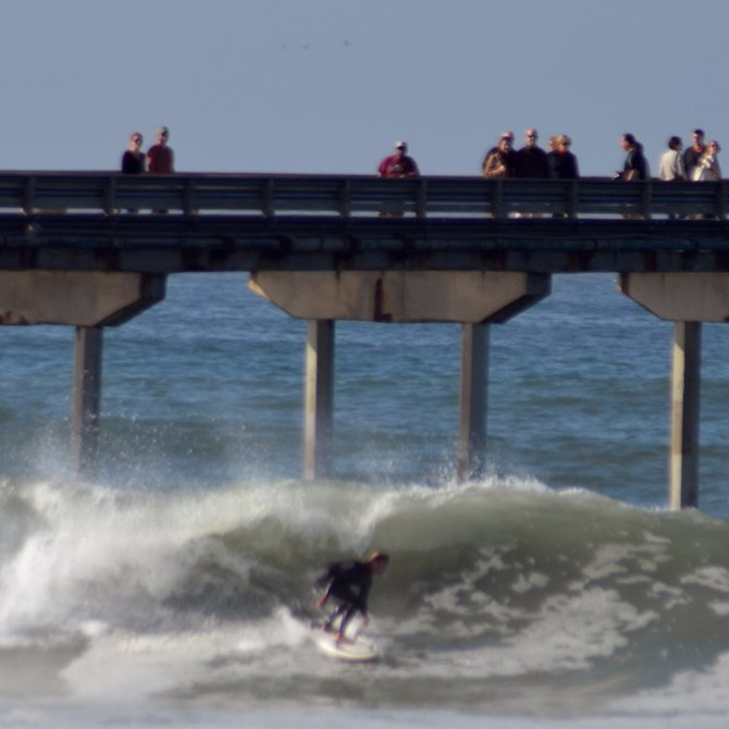 People gather on the pier to watch surfers navigate the winter waves