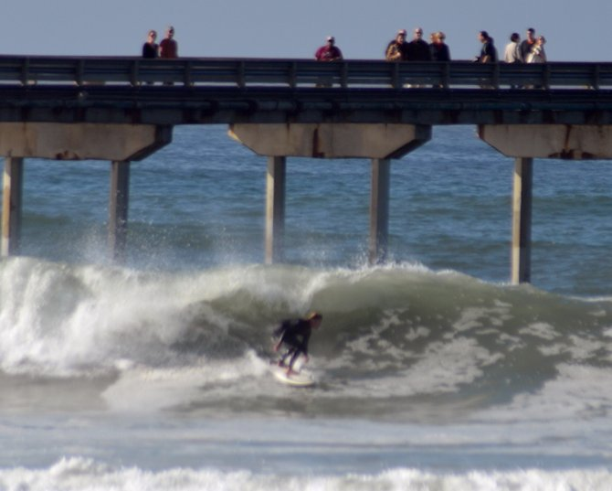 Crowds gather on the pier to watch surfers navigate winter waves in Ocean Beach