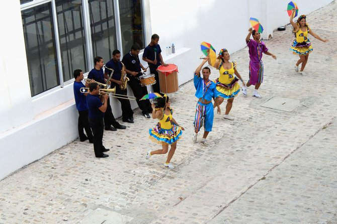 Dancers on the sidewalk, Recife Brazil.  In Recife Pernambuco their is a unique style of dancing which includes colorful costumes and small umbrellas.