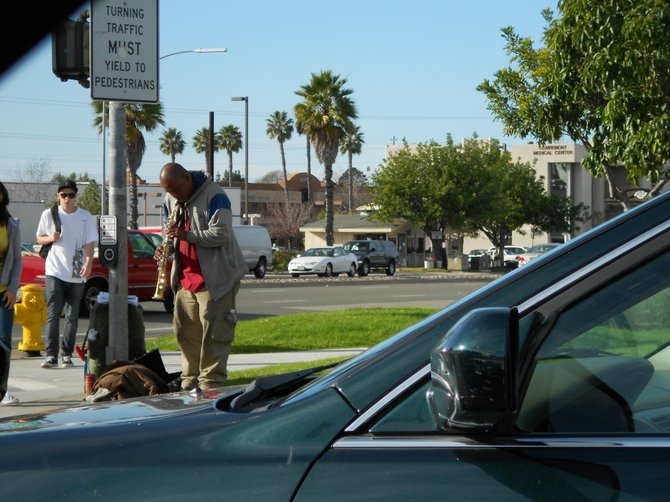 Gentleman performing music at the busy corner of Balboa and Genesee Avenues.