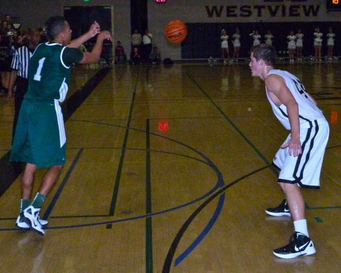 Poway guard Derek Babiash fires a pass with Westview forward Patrick Govea defending