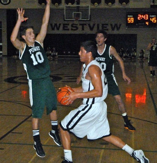 Westview guard Cody Williams looks to pass the ball by leaping Poway guard Tom Erb in the backcourt