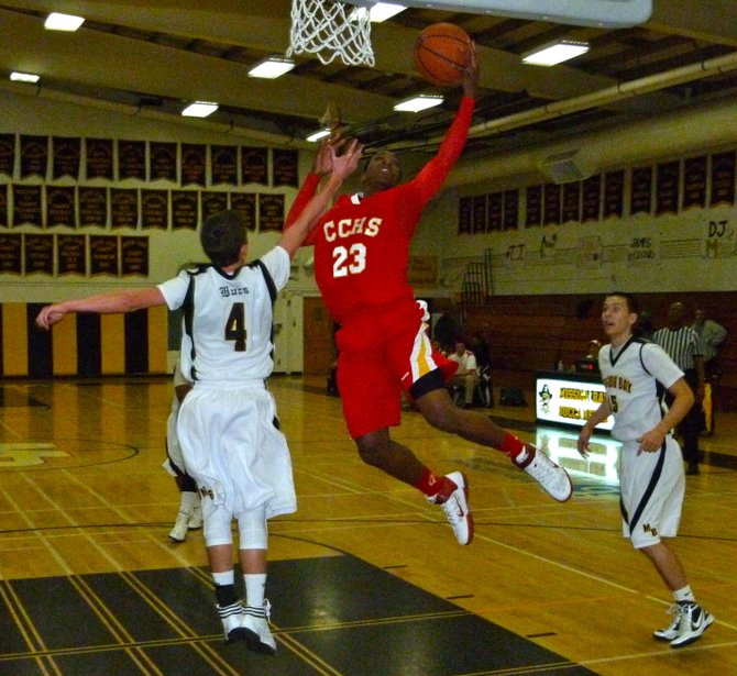 Cathedral Catholic forward Xavier Williams elevates to the hoop between Mission Bay guards Jared Kane (left) and Dylan Holler (right)