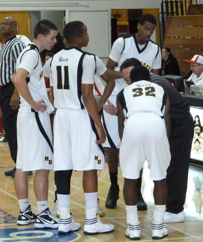 Mission Bay huddles up on the floor around head coach Dennis Kane during a timeout