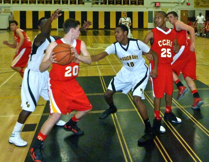 Cathedral Catholic forward Nick Prunty swarmed by Mission Bay guards Vince Petties-Wilson (left) and James Cloud underneath the basket