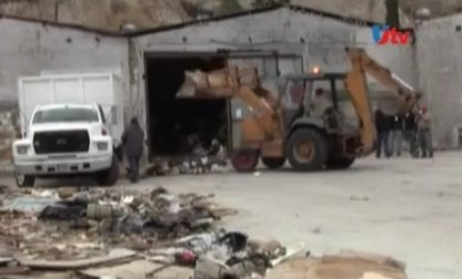 A backhoe removes garbage from a Tijuana warehouse