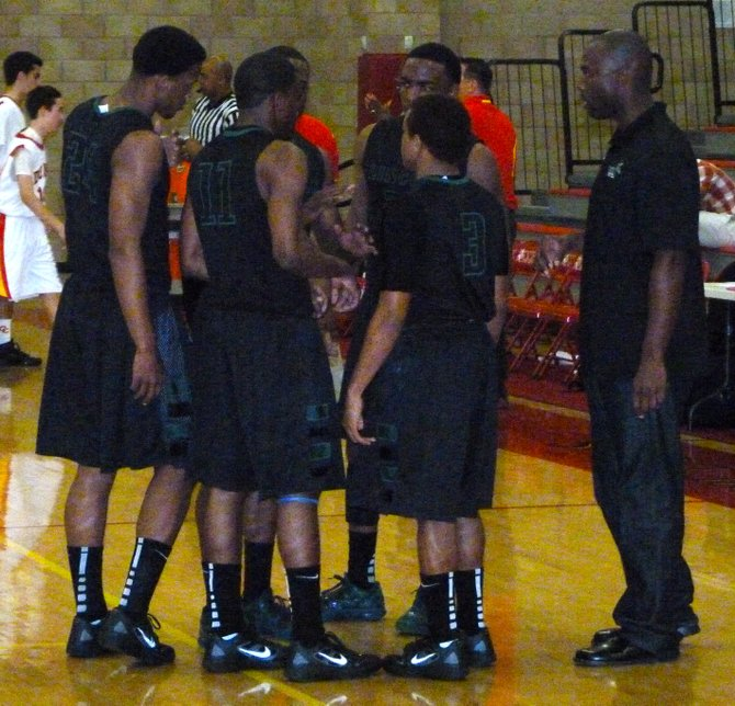 Lincoln starters talk things over with Hornets head coach Jason Bryant before tipoff