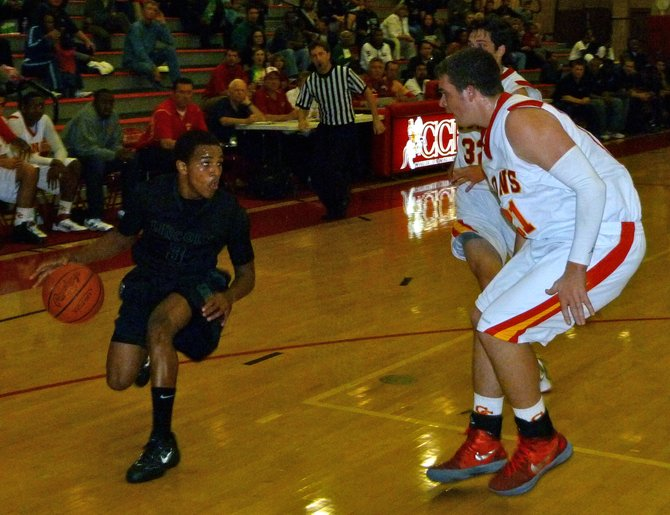 Lincoln guard Keone Spates dribbles on the perimeter with Cathedral Catholic forward Brendan Reh defending