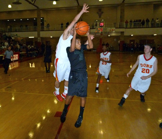 Lincoln guard Keone Spates ducks under Cathedral Catholic guard Michael Rosenburg in the key