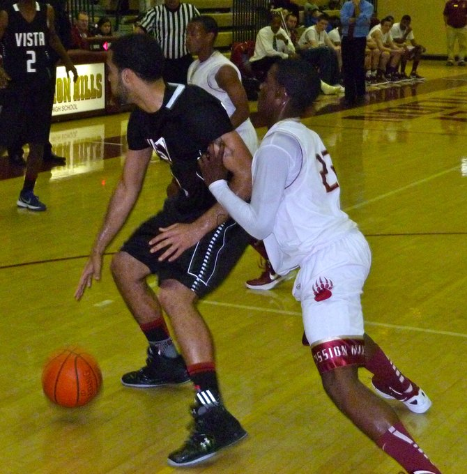Vista guard Sedrick Childress posts up Mission Hills guard Dolyn Hall in the low block