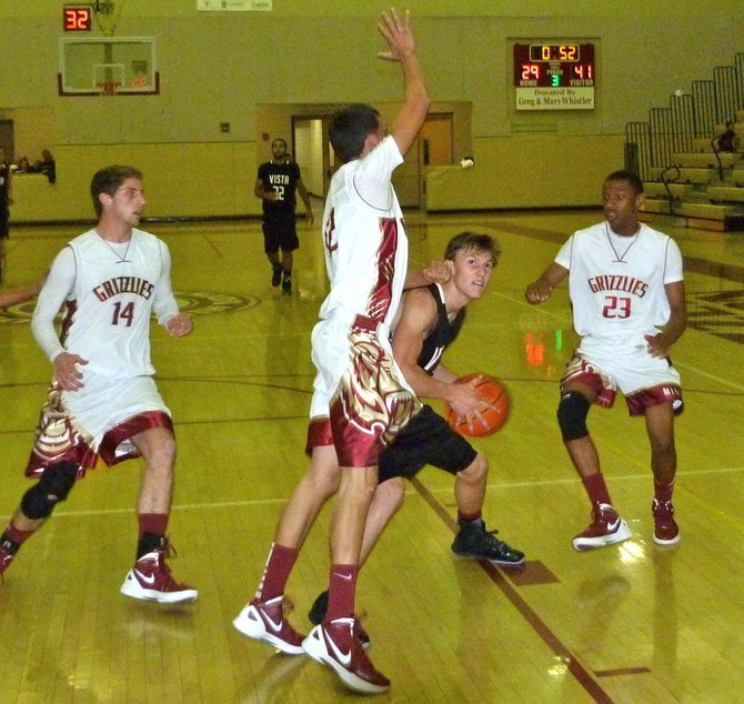 Vista forward Collin Nyenhuis looks to the basket between three Mission Hills defenders