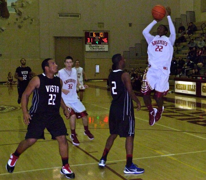 Mission Hills guard Dolyn Hall shoots a jumper over Vista guard John Fletcher