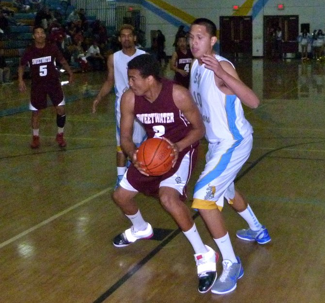 Sweetwater forward Raven Middleton protects the ball from San Ysidro forward Fernando Ahumada underneath the basket