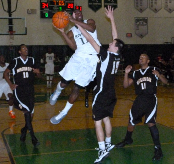 Lincoln guard Jerry Cobb puts up a twisting shot over Mission Bay guard Dylan Holler