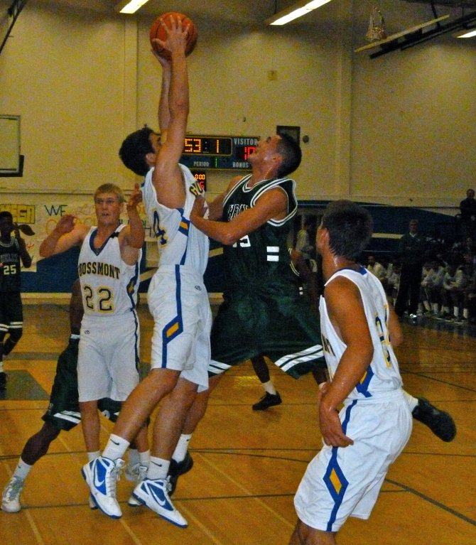 Grossmont forward Derek Rustich absorbs contact from Helix forward Brian Valadez in midair while pulling down a rebound