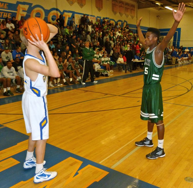 Helix forward Romario Wilson guards Grossmont guard Austin Swisher on an inbounds pass