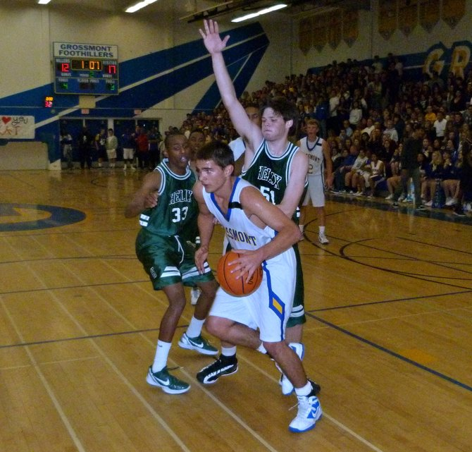 Grossmont Robby Nesovic dribbles the ball in the lane between Helix guard Michael Todd (33) and forward William Mildenhall