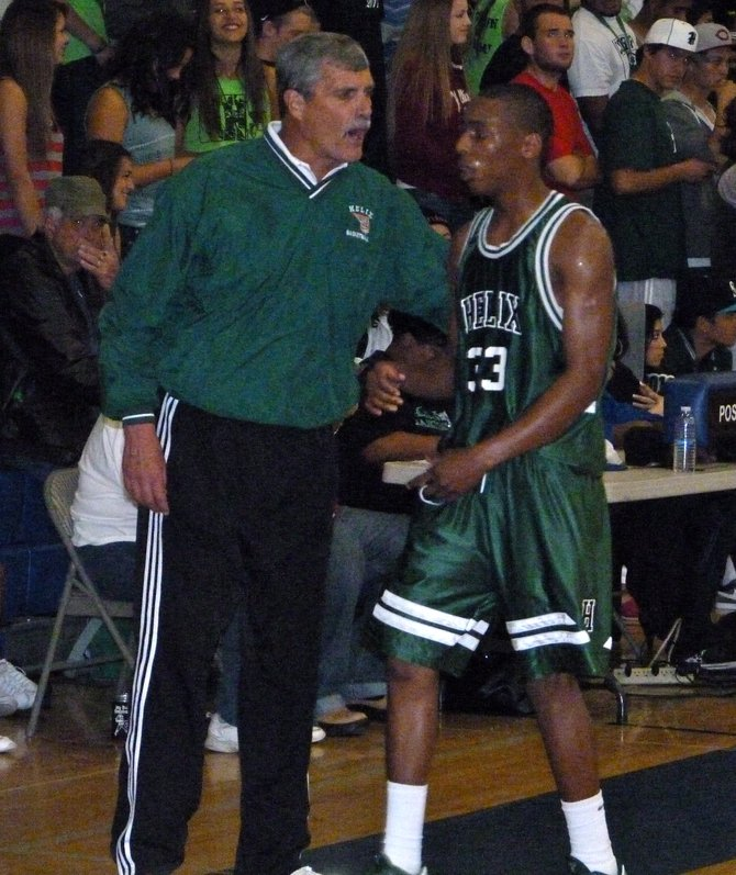 Helix head coach John Singer instructs Highlanders guard Michael Todd along the sideline