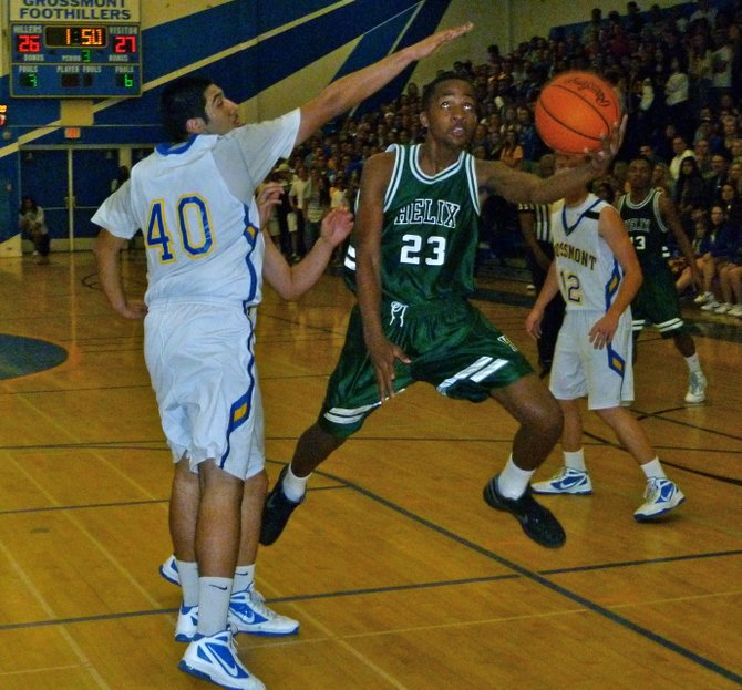 Helix forward Kaelen Mitchell drives past Grossmont forward Bilal Rahim to set up an acrobatic shot attempt