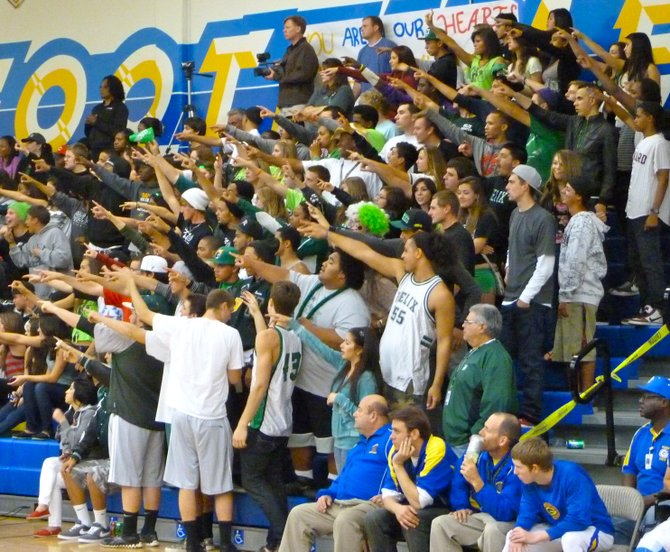 Helix's student section puts its arms up during a Highlanders free throw attempt