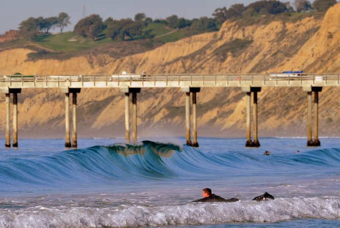 Fun little shore break wave at Scripps Pier in La Jolla, with Torrey Pines Golf Course in the background.