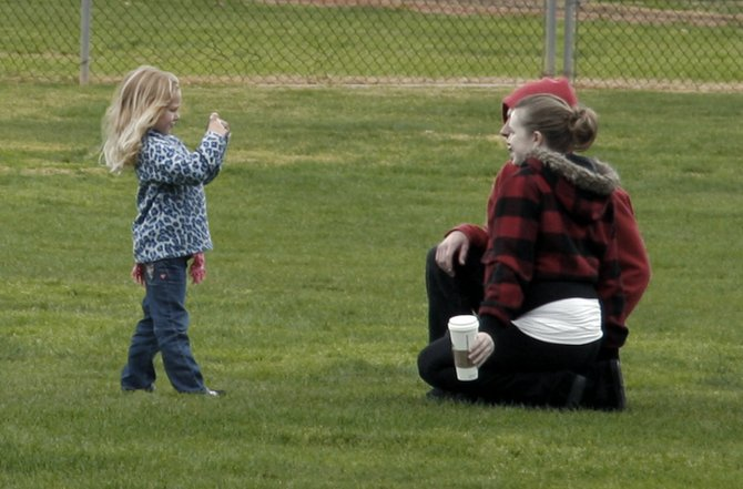 A little girl snaps a picture of her parents at a park in Poway, CA