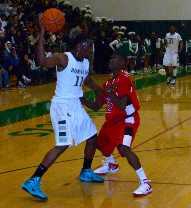 Lincoln guard Jerry Cobb shields the ball from Hoover guard Jonathan Booker in the backcourt
