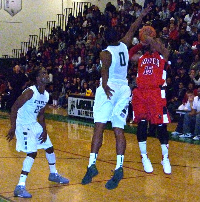Hoover guard Chris Jones shoots a jumper in the midst of Lincoln guards Tyree (23) and Tyrell Robinson