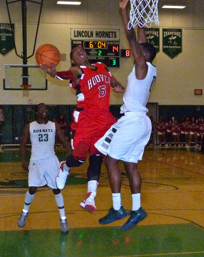 Hoover guard Chris Jones twists in the lane for a scoop shot against Lincoln guard Tyrell Robinson
