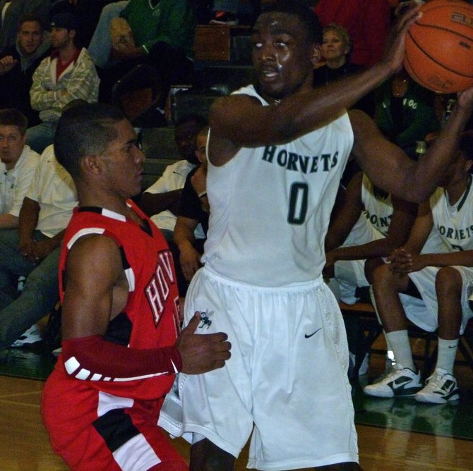 Lincoln guard Tyrell Robinson protects the ball from the defensive pressure of Hoover guard Chris Jones