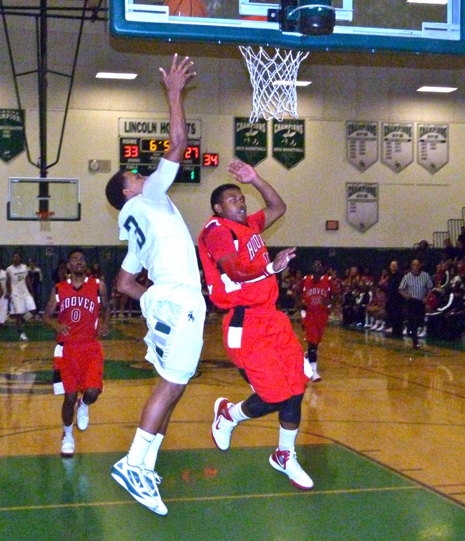 Lincoln guard Keone Spates lays the ball up over Hoover guard Damonte Holiday