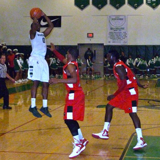 Lincoln guard Tyrell Robinson shoots a jumper with two Hoover players defending closely