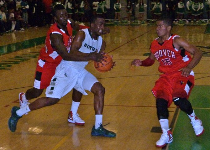 Lincoln guard Tyrell Robinson drives between Hoover forward Jeremai Northard (left) and guard Chris Jones