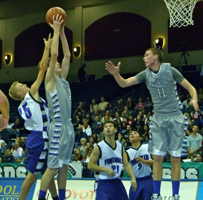 The Rock guard Holden Haskett hauls in a rebound over Foothills Christian guard Johnny Van Ommering
