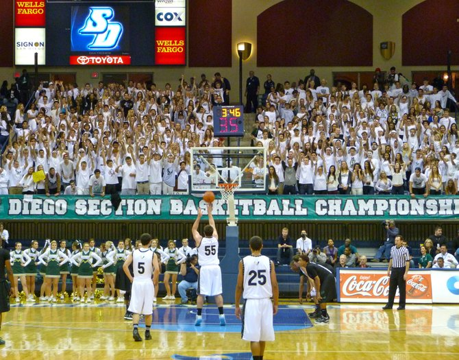 La Costa Canyon's white-clad student section puts its arms in the air during an Erik Magnuson free throw attempt