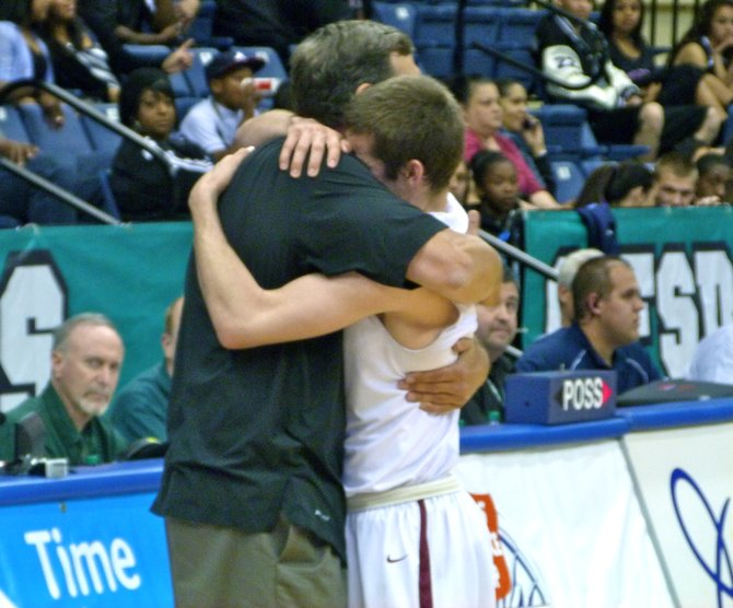 Torrey Pines head coach John Olive and Falcons guard Joe Rahon share an embrace as the Falcons wrap up the Division I championship
