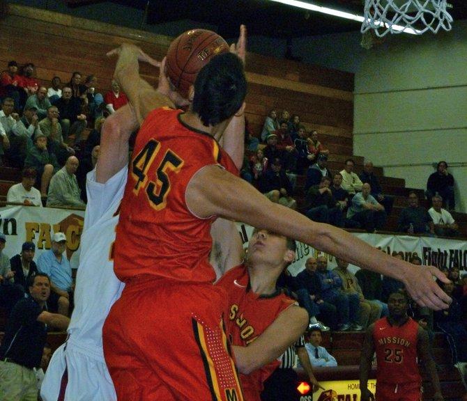 Mission Viejo center Sage Stone blocks the shot attempt of Torrey Pines forward Sam Worman under the basket