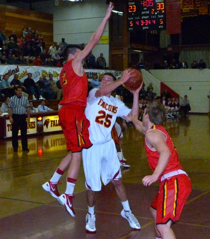 Torrey Pines forward Sam Worman elevates to the basket between Mission Viejo guards Michael Cramer (left) and Austin Reuland (right)