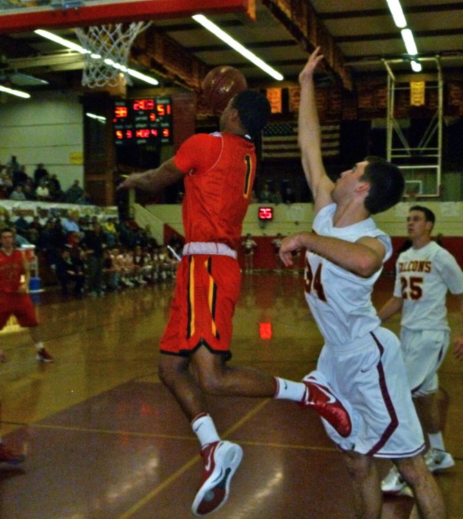 Mission Viejo guard Max Redfield drives past Torrey Pines forward Sean Milmoe to the basket