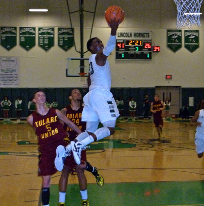 Lincoln guard Tyree Robinson streaks to the basket past two Tulare Union defenders