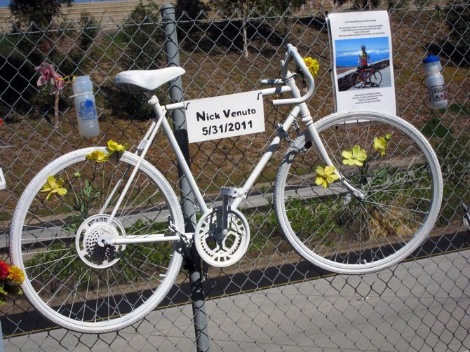 A bike hangs along the fence in PQ on the 56 Bike Path in memory of Nick Venuto who died in a bike/auto collision in May, 2011.